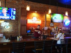 The comfortable interior melds century old brick walls with modern sports bar interior.